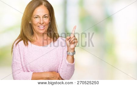 Beautiful middle age adult woman wearing winter sweater over isolated background with a big smile on face, pointing with hand and finger to the side looking at the camera.