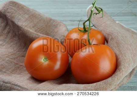Red Tomatoes On A Napkin On A Wooden Background