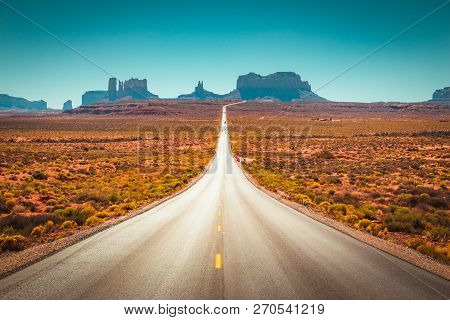 Classic Panorama View Of Historic U.s. Route 163 Running Through Famous Monument Valley On A Beautif