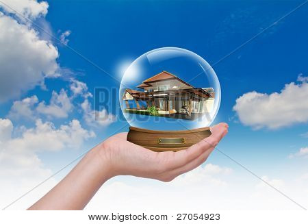 Hand hold snow-dome with home inside against a blue sky