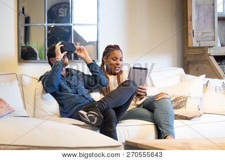 View Of A Young Couple Of Friends, A Caucasian Man Using Virtual Reality Glasses And A Mixed Race Wo