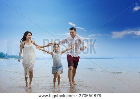 Family on the beach.happy family holiday travel summer.father,mother and daugter are walking hand in
