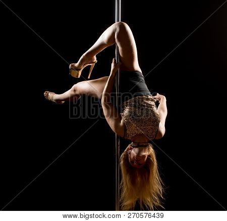 Woman Performs Pole Dance On The Stage. Girl Whirls Around The Pole While Performing Dance Or Yoga