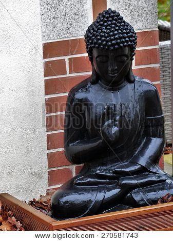 Black Budha In Meditation Sat On The Ground In The Rain Of Day In Front Of A Wall Of Red Brick.