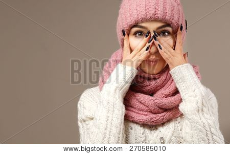 beauty face care portrait of attractive young caucasian woman in warm clothing  studio shot winter hands nails