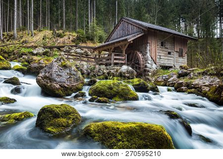 Idyllic Long Exposure View Of An Old Abandoned Mill With Mossy Rocks Lying In Beautiful Riverbed In
