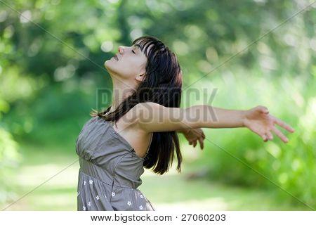 happy teenage girl breathing in wild nature