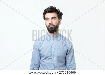 Weary Hispanic Man In Blue Shirt Rolling His Eyes Up.