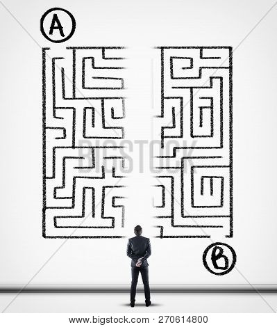 Thoughtful Businessman Solving A Maze Using A Shortcut. Maze Drawn On A White Wall. Point A To Point
