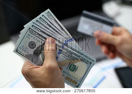 Male Hand Holds Dollar Banknotes And Plastic Bank Card In Hands Closeup. Cash Out Money Earned On We