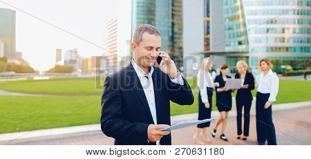 Businessperson Talking By Smartphone With Employees In Backgroun