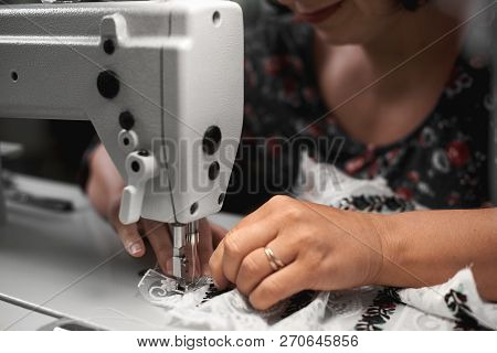 Close-up Of Female Seamstress Hands Connecting White Fabric Details With Floral Colorful Embroidery