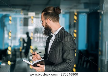 Smiling Man Writing In Daily Planner To Keep Track Of Business Agenda And Timetable.