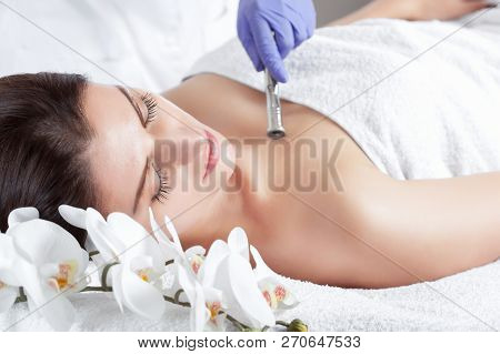 poster of The cosmetologist makes the Microdermabrasion procedure of the facial skin of a beautiful, young woman in a beauty salon.Cosmetology and professional skin care.