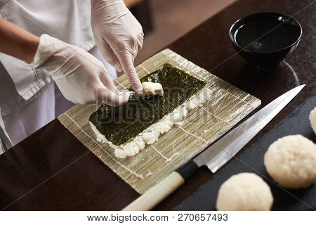 Close-up Of Chef Hands Preparing Japanese Food. Japanese Chef Making Sushi At Restaurant.
