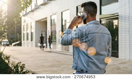 Rear View. Hipster Businessman With Beard, In Denim Jacket And Trendy Glasses Walks Around City And
