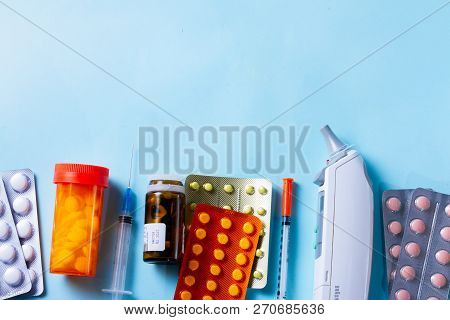 Healthcare Concept - Pills And Medical Thermometr Boder On Blue Background