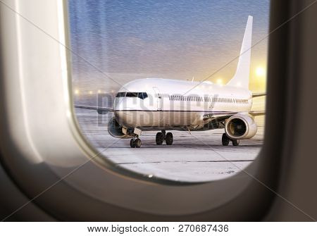 white aircraft in airport at non-flying weather, view  through window