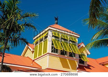Mansard With Open Yellow Window Shutters And Pineapple On Terracotta Roof On Sunny Day On Blue Sky I
