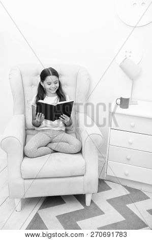 Reading is her hobby. Girl child sit yellow armchair read book. Kid prepare to go to bed. Pleasant time in cozy bedroom. Girl kid long hair cute pajamas relax and read fairytale book before sleep. poster
