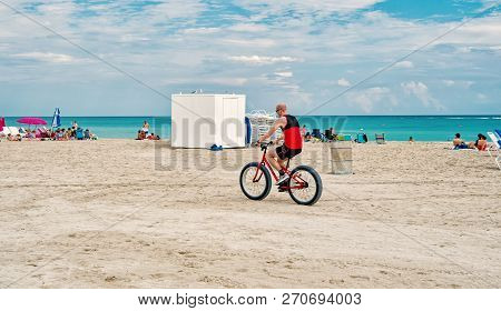 Miami, Usa - January 10, 2016: Man Or Biker Riding Bicycle On South Beach Along Blue Sea Or Ocean Co