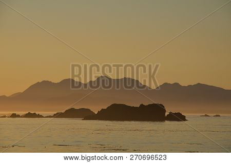 Orange Haze Of Setting Sun Makes Silhouettes Of Mountains Of Brookes Peninsula And Rocks Of Reef In