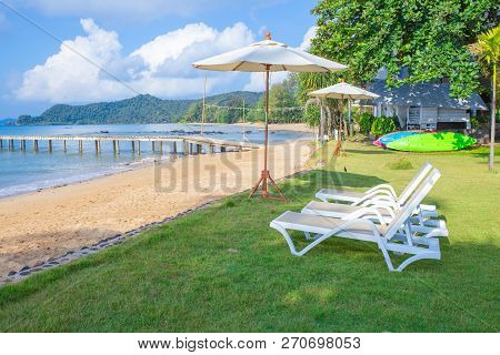 Beach Chairs And Beach Umbrellas Are On The Lawn At The Beach.sea View, Bridge And Mountain And Brig