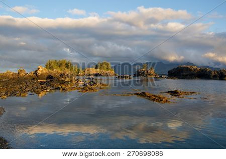 Early Morning Sun Warms Rocky Islets And Clouds Near Brookes Peninsula, Vancouver Island, Bc