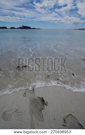 Footprints In Sand Being Erased By An Incoming Wave On A Sunny Beach On The Brookes Peninsula, Vanco