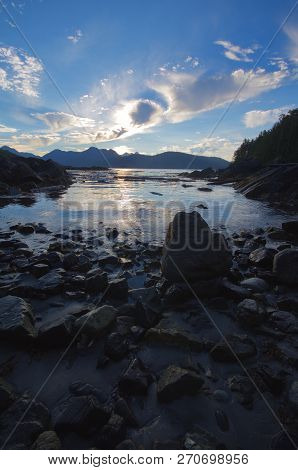 Blue Sky And Wispy Clouds Reflected In Calm Bay At Low Tide With Rocks In Foreground, Brookes Penins