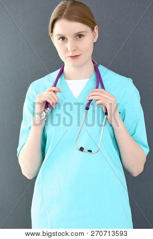 Doctor Woman Portrait With Stethoscope. Young Female Surgeon Or Nurse  Standing Near Grey Wall  In C