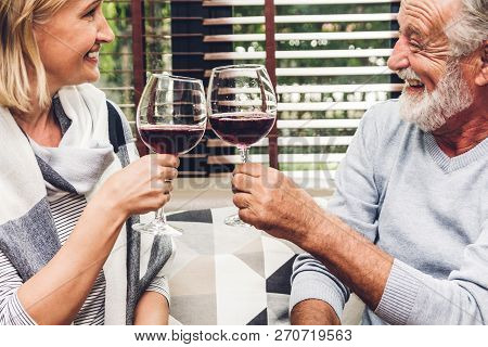 Senior Couple Relax Talking And Drinking Wine Glasses Together On Sofa In Living Room At Home.retire