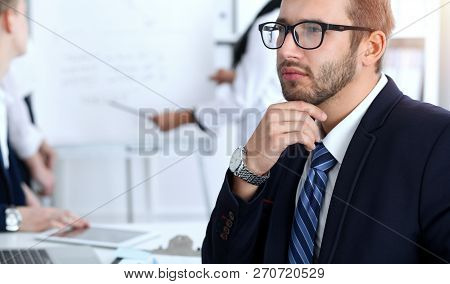 Business People At Meeting In Office. Focus At Cheerful Smiling Bearded Man Wearing Glasses. Confere