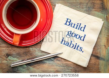 build good habits - inspirational handwriting on a napkin with a cup of tea