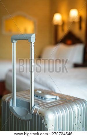 Close Up Gray Silver Travel Suitcase Is In An Unoccupied Hotel Room And There Is White Linen Cover.