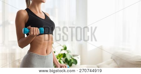 Weight Exercise. Slim Girl Exercising With Dumbbells At Home Interior, Copy Space
