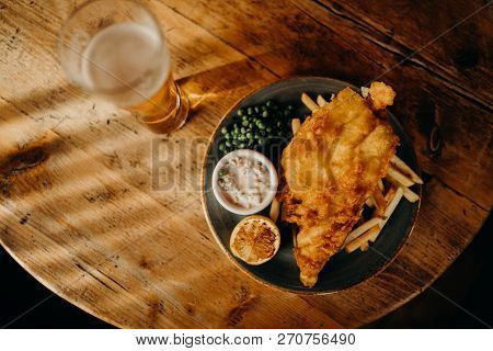 Fish And Chips Plate And Pint Of Beer On A Wooden Table Viewed From Above.