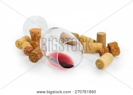 Wine Glass Lying On Its Side With Small Amount Of Red Wine Among Of Different Wine Cork On A White B