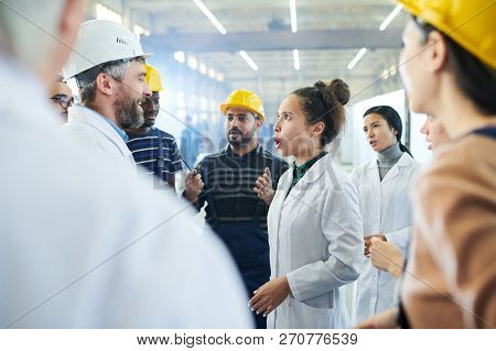 Side View Portrait Of Female Factory Worker Shouting At Senior Manager During Strike In Industrial W