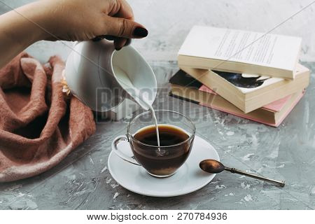 Still Life With Cup Of Drink,creamer And Books, Female Hand With Creamer Pours Milk In Coffee Cup