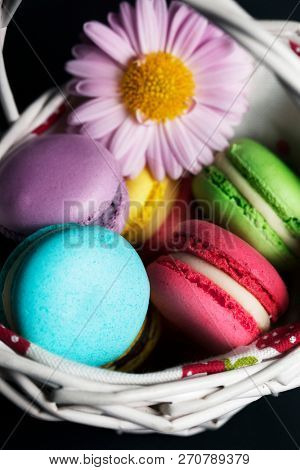 Sweet and colourful french macaroons in the basket.