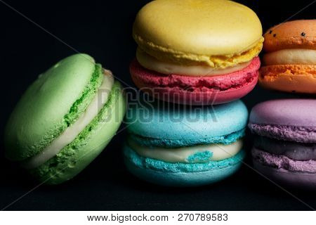 Pile of macaroons on black background.