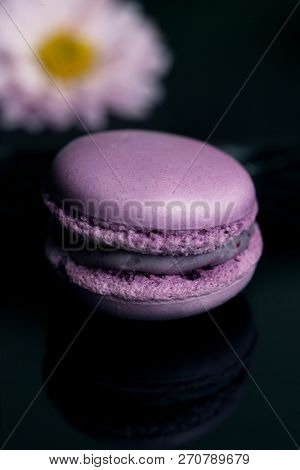 Sweet purple macaroon isolated on black background.