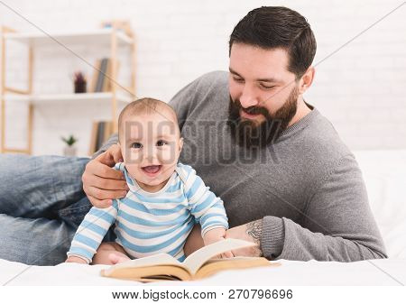 Young Man Babysitting. Bearded Father Reading Book To His Adorable Baby Son