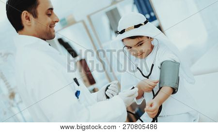 Arabic Male Doctor Checking Blood Pressure Boy. Child At The Pediatrician. Hospital Concept. Healthy