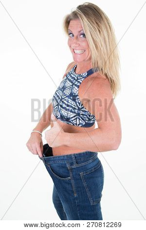 Blonde Woman Shows Her Weight Loss By Wearing An Old Jeans Isolated On White Background