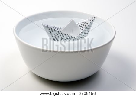 Paper Boat In Bowl Full Of Water