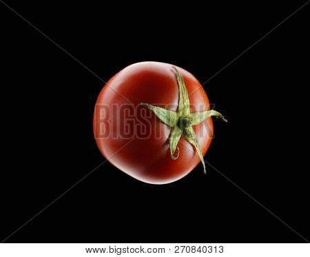 Red tomato on dark background, isolated on black.