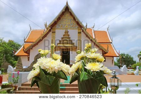 Closed Up A Pair Of Flower Bouquets For Offering Lord Buddha With Blurred Wat Phumin Temple In Backg