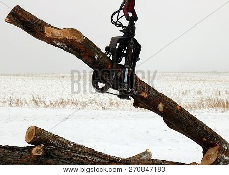 Close up of grappling hook moving logs in a snow squall poster